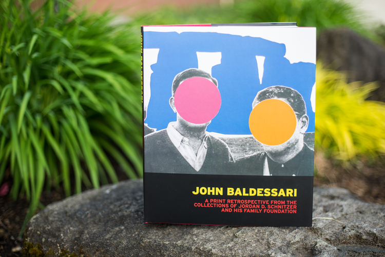 Photo of John Baldessari: A Print Retrospective from the Collections of Jordan D. Schnitzer and His Family Foundation book standing up on a rock outdoors
