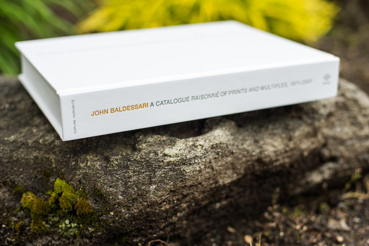 Photo of John Baldessari: A Catalogue Raisonné of Prints and Multiples 1971-2007 book, spine facing out, sitting on a rock outdoors