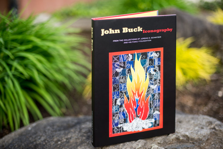 Photo of John Buck: Iconography book standing up on a rock outside