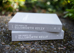 Photo of both volumes of The Prints of Ellsworth Kelly, laying on a rock outdoors, spines facing out