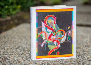 Photo of Frank Stella: Prints book standing up on a rock outdoors