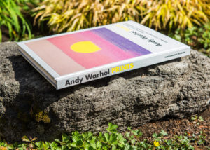 Photo of Andy Warhol Prints book laying on a rock outdoors, spine and cover visible