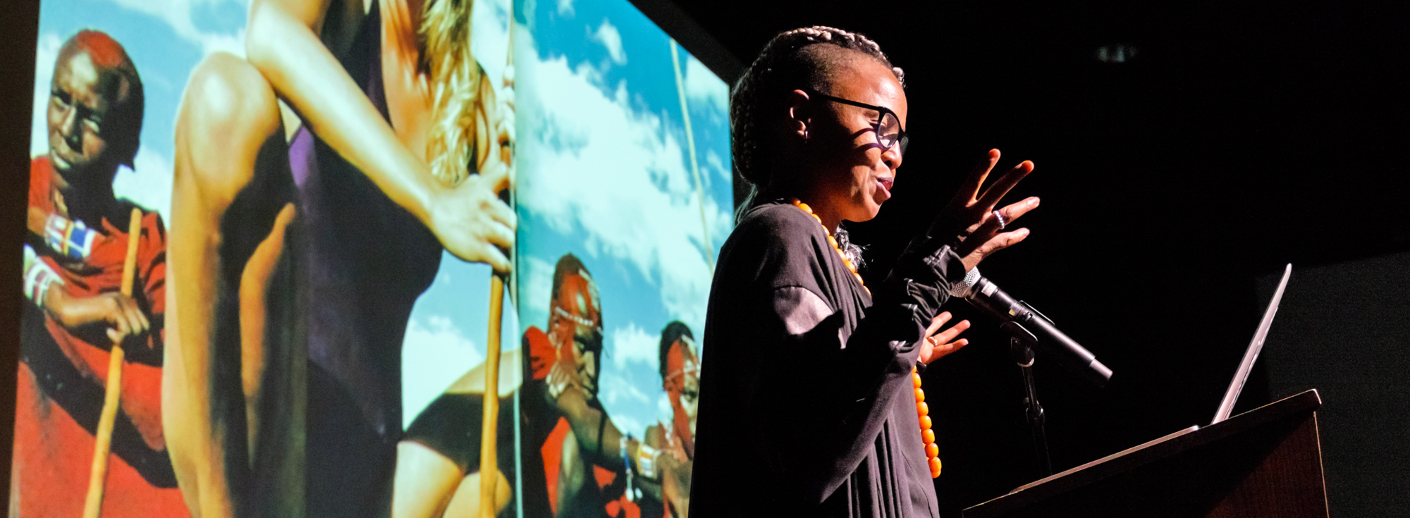 Wangechi Mutu speaking at a podium with microphone in front of a projected image