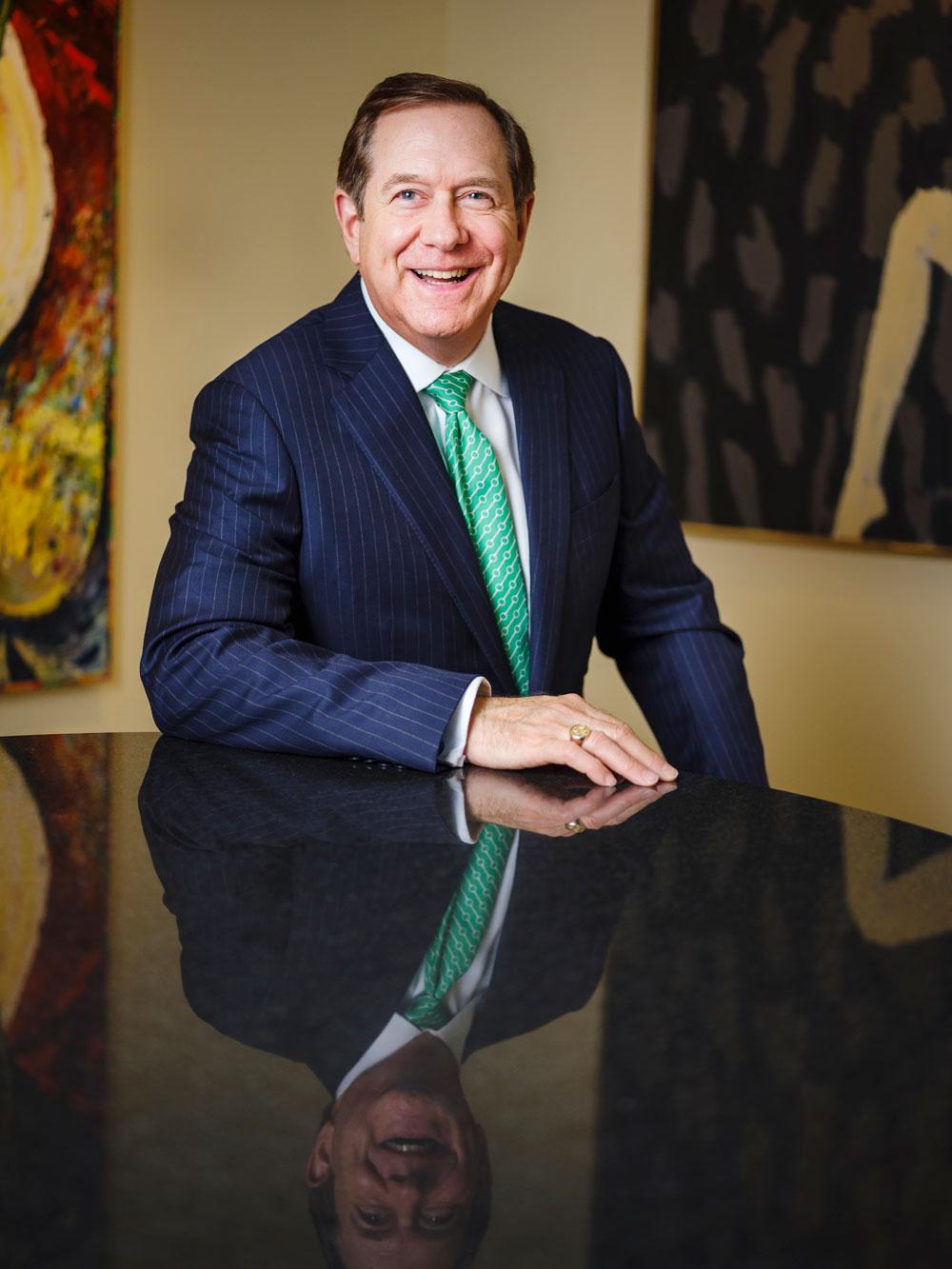 Headshot of Jordan D. Schnitzer, smiling at a black table